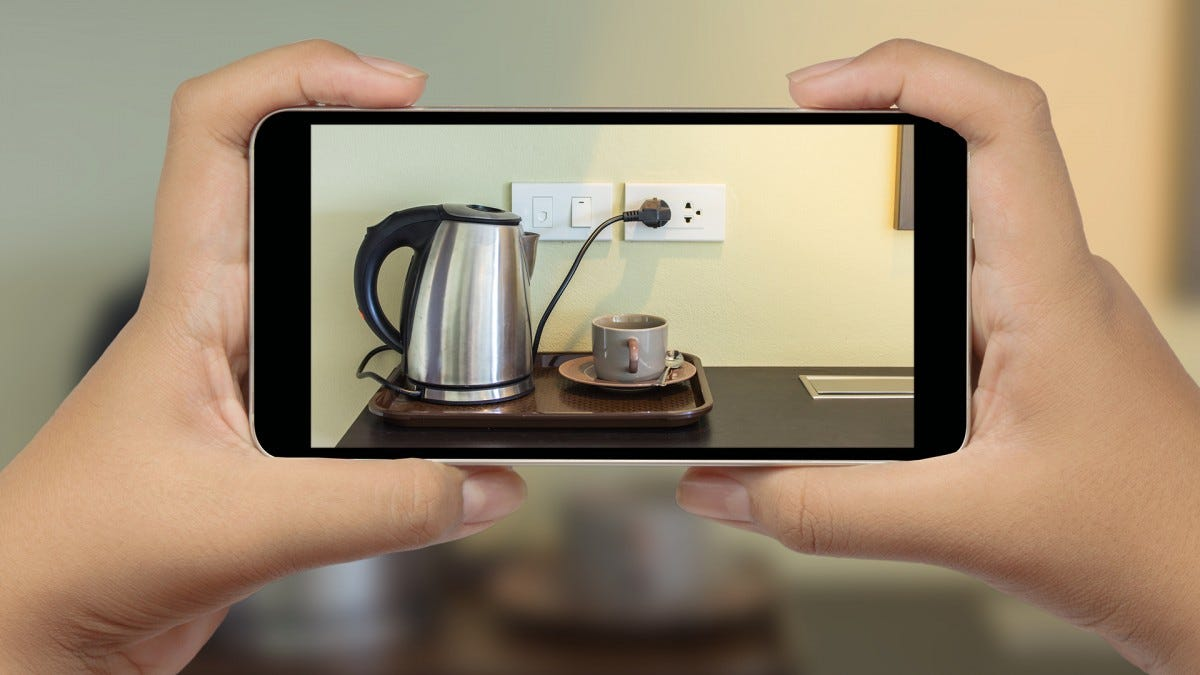Hands holding a phone and taking a photo of a coffee pot.