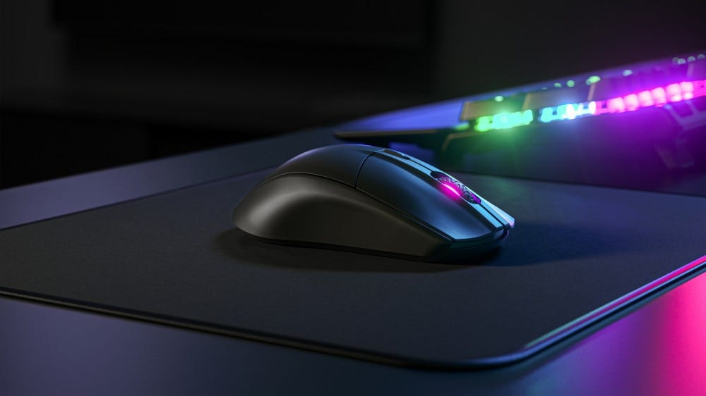 SteelSeries Rival 3 wireless mouse on a black mouse pad with neon lights in the background