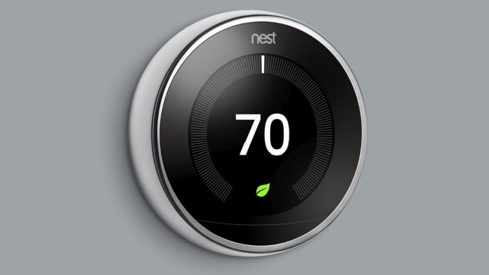Nest Learning Thermostat, 3rd generation, mounted on a gray wall