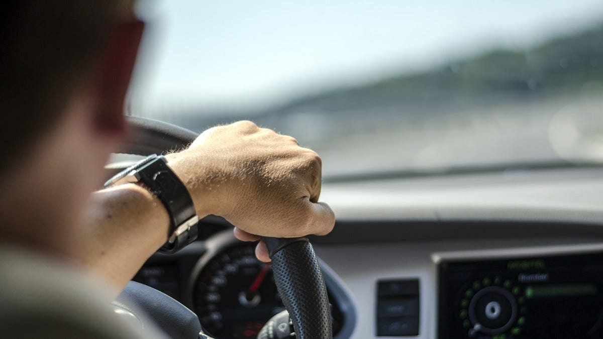 A man's hand on a steering wheel.