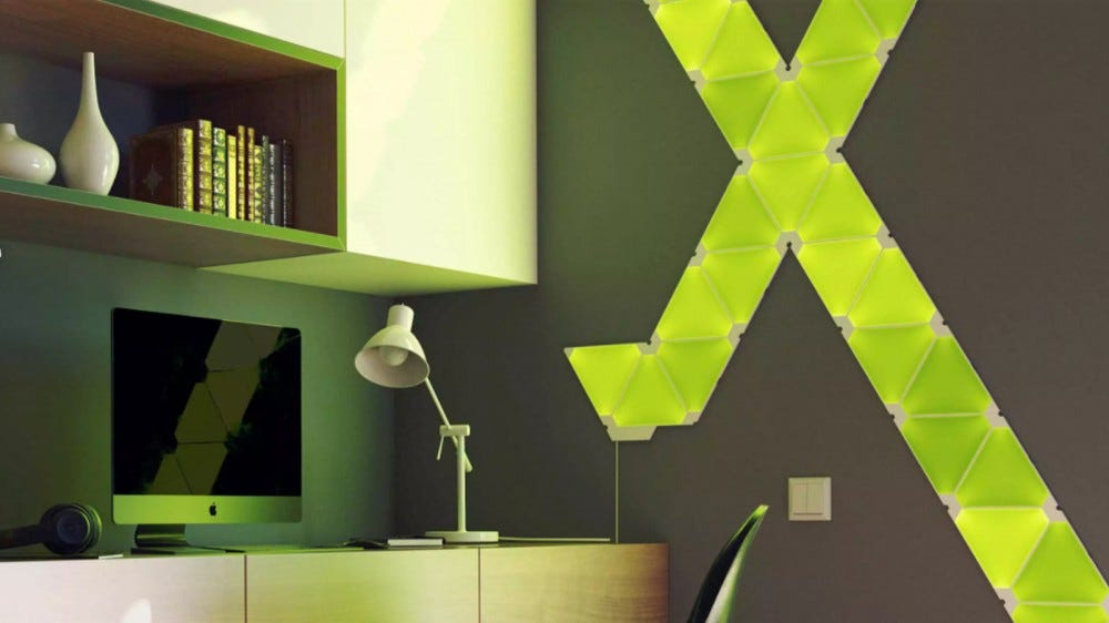 Yellow-green Nanoleaf color panels mounted in an X shape on a wall in a home office