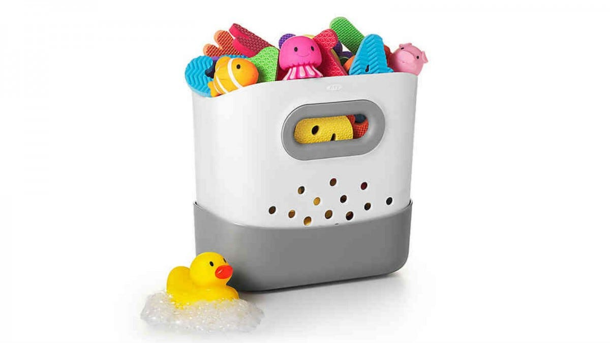 A rubber duckie sitting next to an OXO Tot Stand Up Bath Toy Bin filled with bath toys.