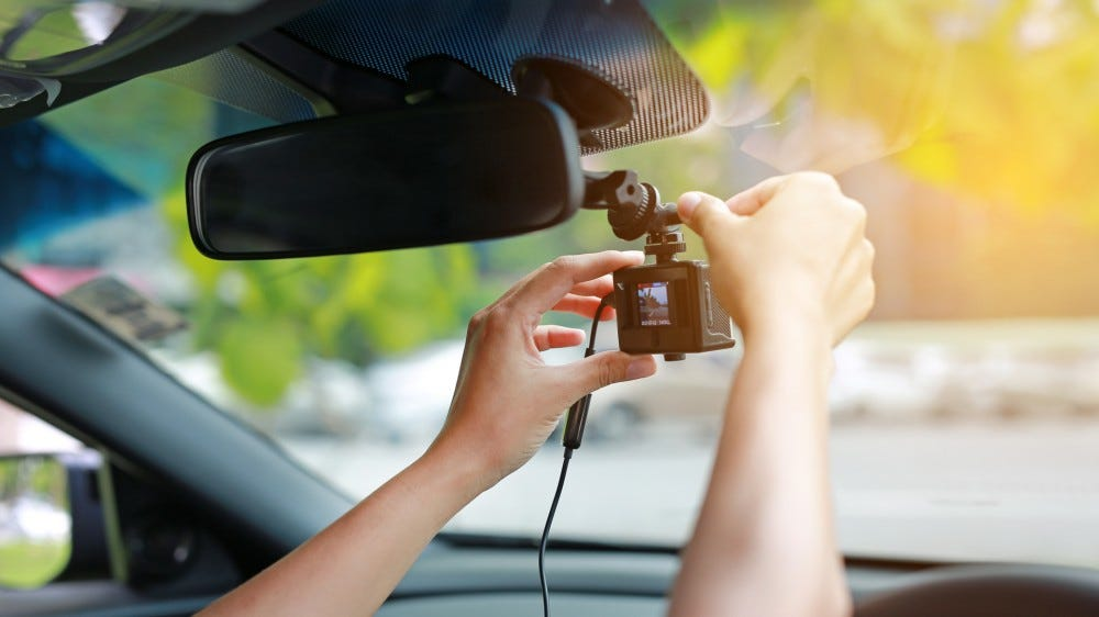 Hands installing front dash cam recorder on windsheild