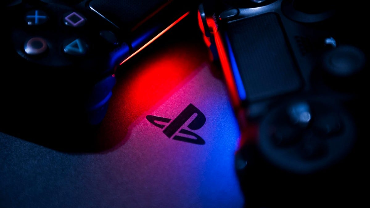 The Sony PlayStation Logo illuminated in blue and red by the glow of the dualshock 4's light bar