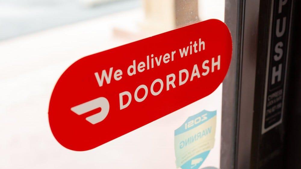 A closeup of a Doordash sticker on a restaurant door.