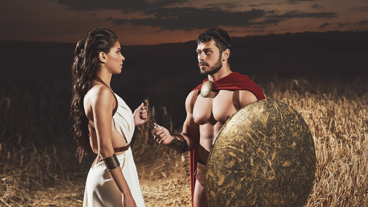A couple dressed as spartan warriors having a conversation in the battlefield.
