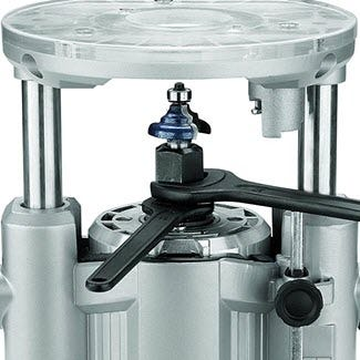A plunge router with two wrenches adjusting the collet.