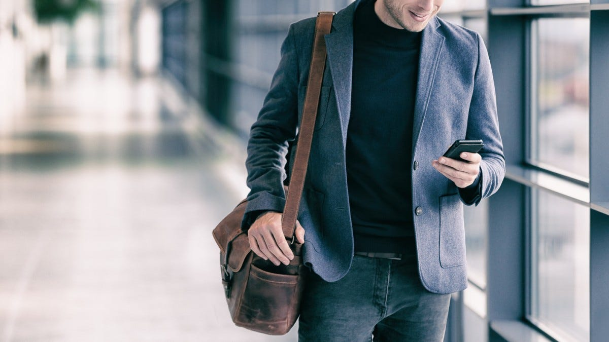 A man looking at his phone and carrying a messenger bag on his shoulder.