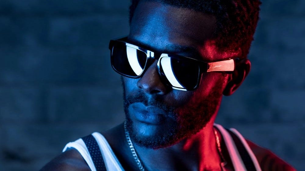 A model wearing the Bose Tenor in dark and mysterious red/blue lighting. It's very becoming.