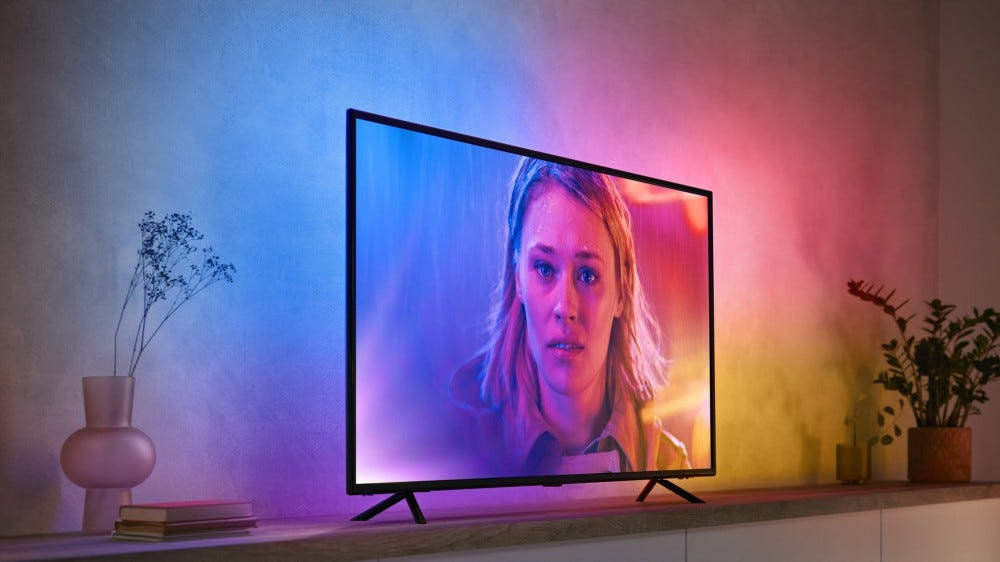 A TV with several shades different color lights shining from the back.