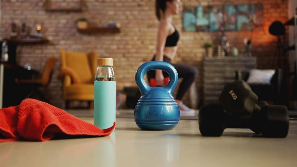 A woman exercising, framed by a foreground of exercise tools like kettle bells and weights.