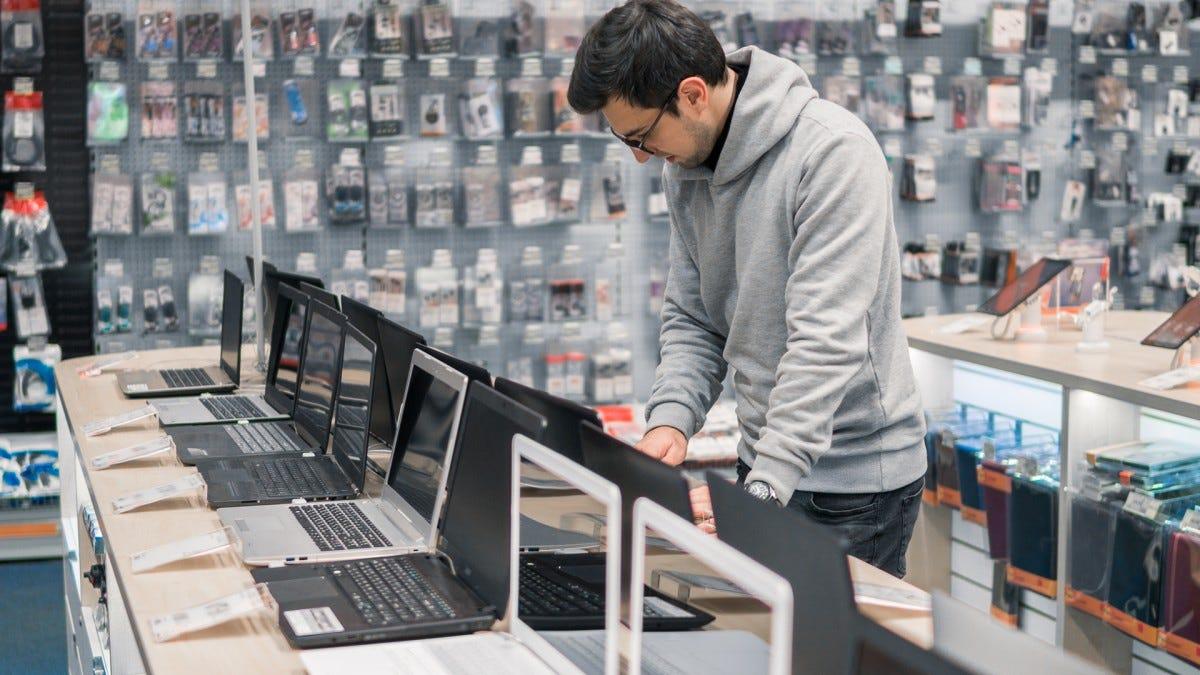Un uomo che guarda i computer portatili in un negozio.