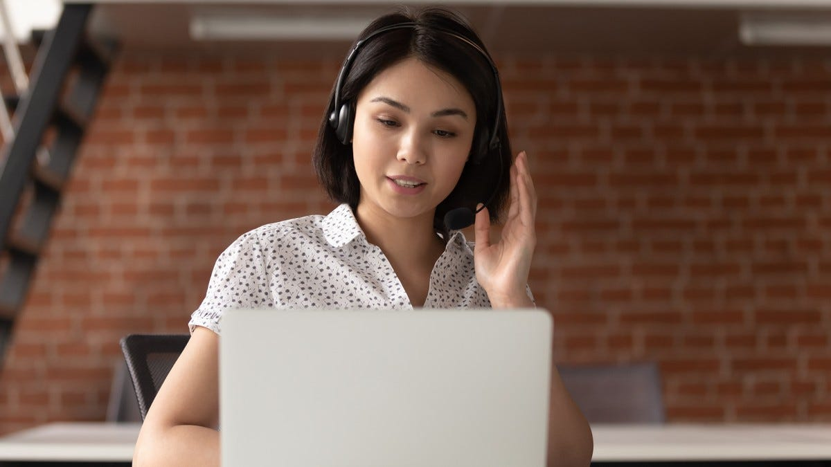 A woman watches a video while wearing wireless headphones.