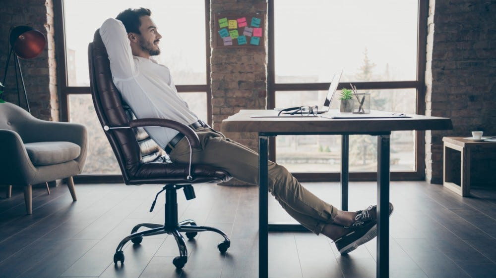 Profile side view of person leaning back relaxing in office chair at desk in modern office