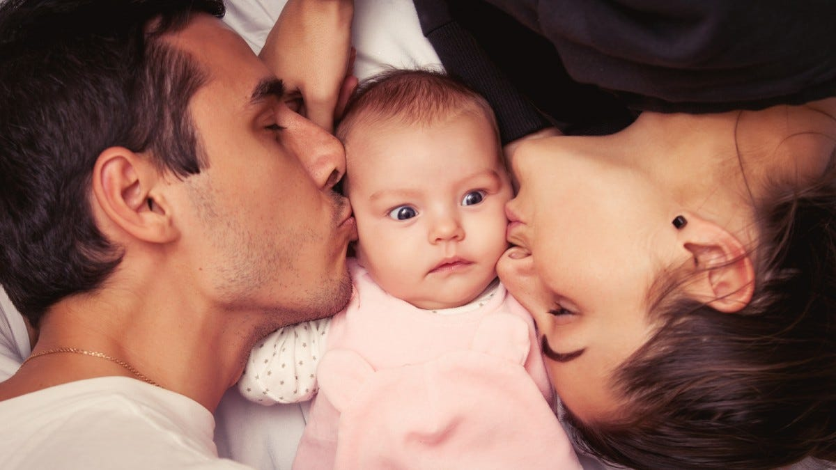 A couple kissing a little baby.