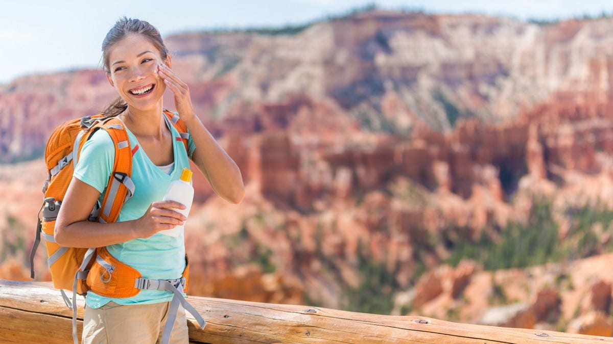 A woman applies facial sunscreen while hiking.