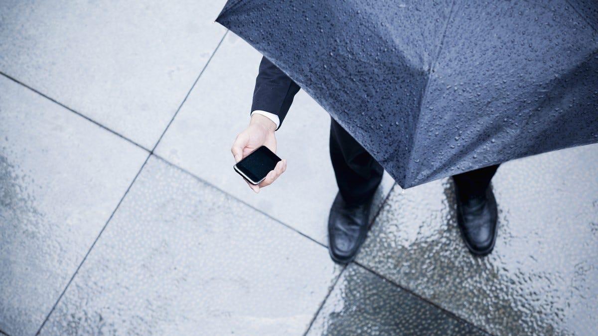 A man checks his phone in the rain.