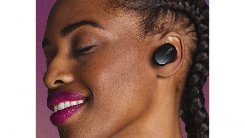Young woman wearing the new Bose QuietComfort Earbuds against a pink background