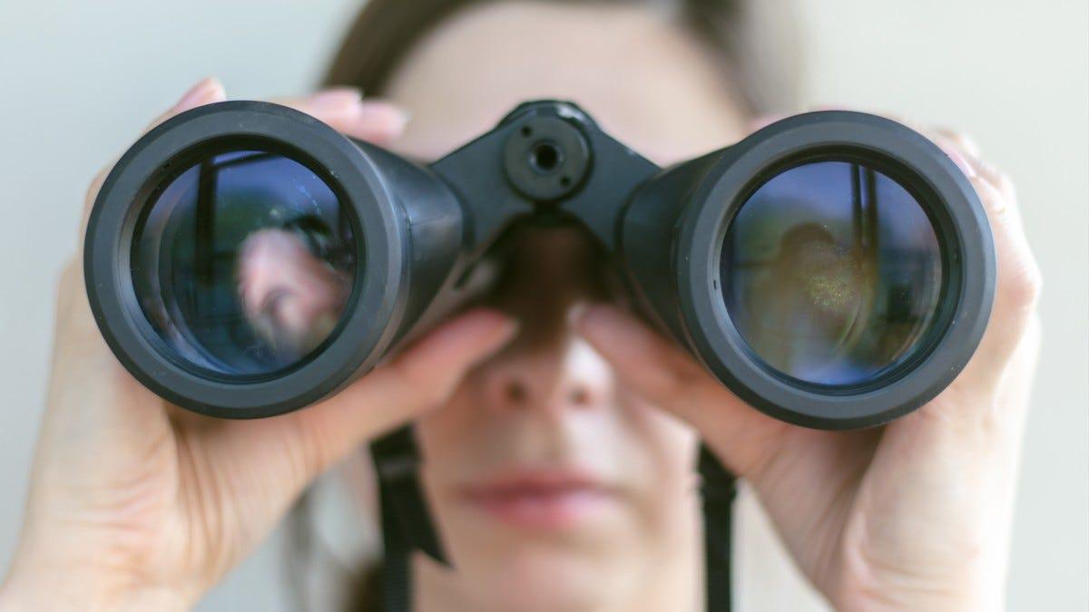 Una donna che osserva tramite il binocolo.