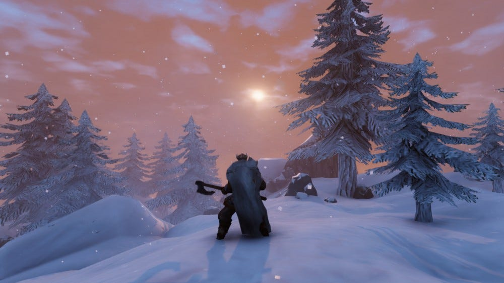 A player character standing against the sun on a snowy mountain in 'Valheim'