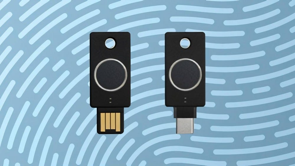 Two Yubikeys, one in USB-A the other in USB-C, with fingerprint sensors, laid on a fingerprint patterned background.