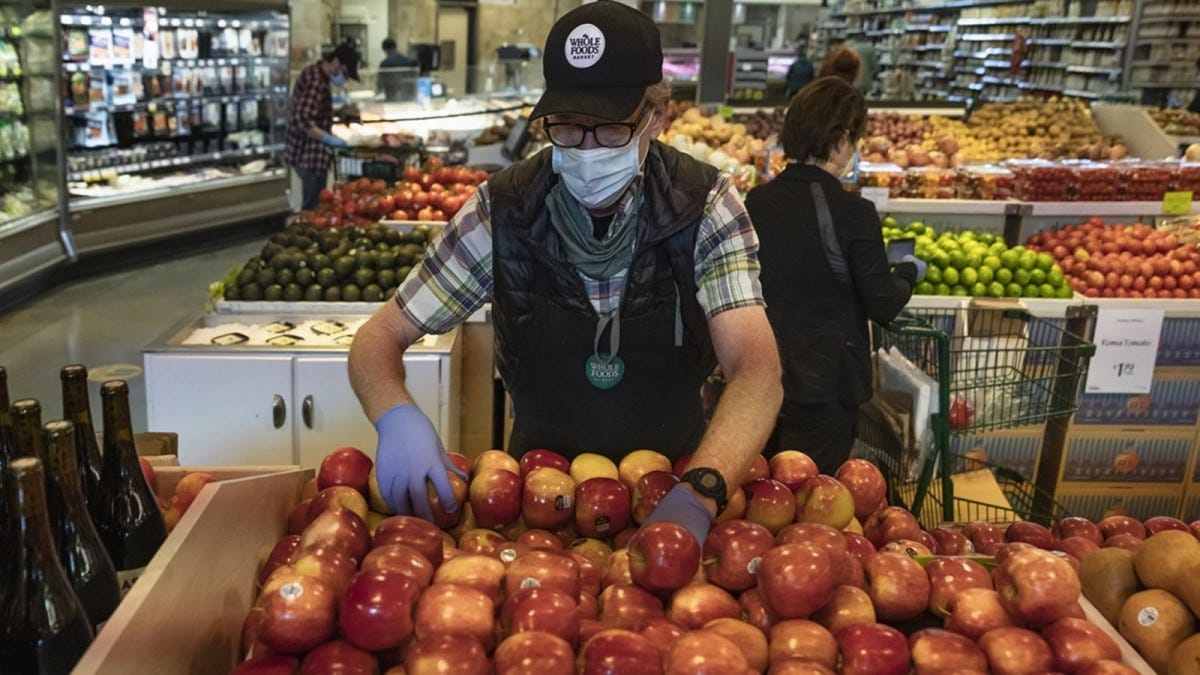 A Whole Foods employee wearing a mask and restocking apples.