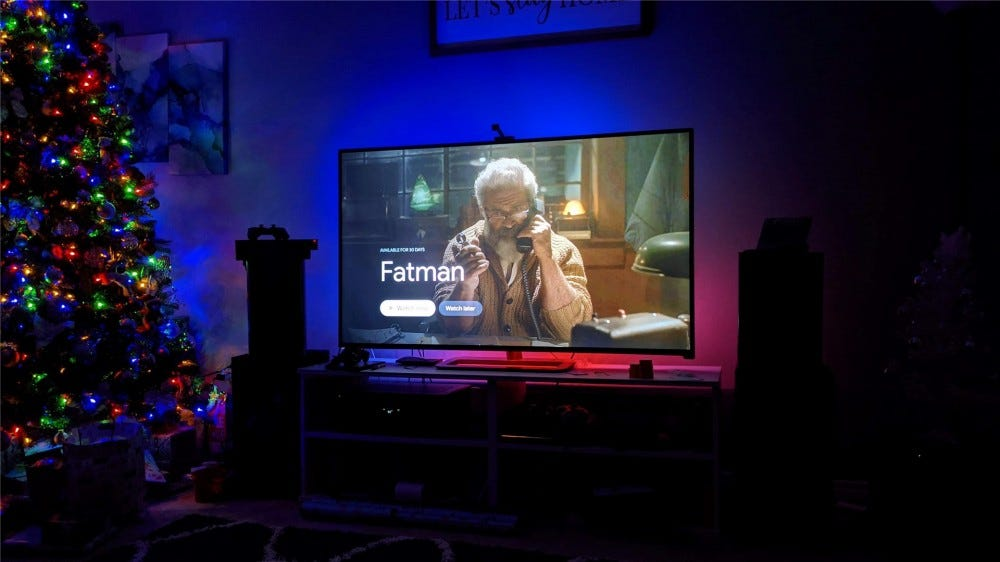"A preview image for the movie ""Fatman"" with the Immersion glowing blue and pink behind the TV"