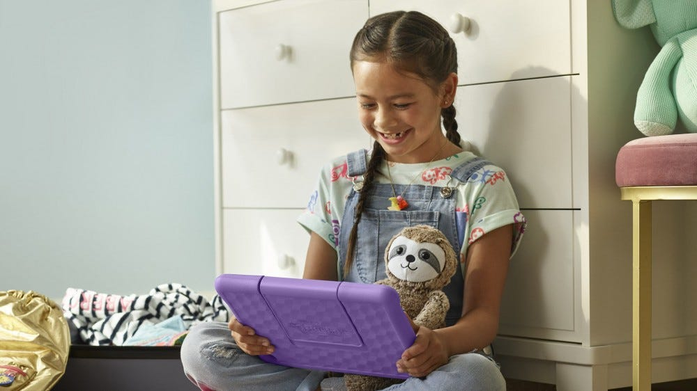A young girl looking at an Amazon Kids+ Fire Tablet