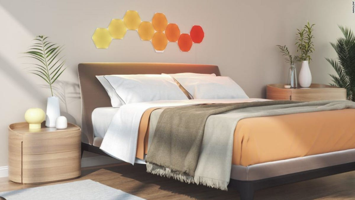 A bed in a modern bedroom, with 9 hexagonal LED panels lit in varying shades of yellow and orange.