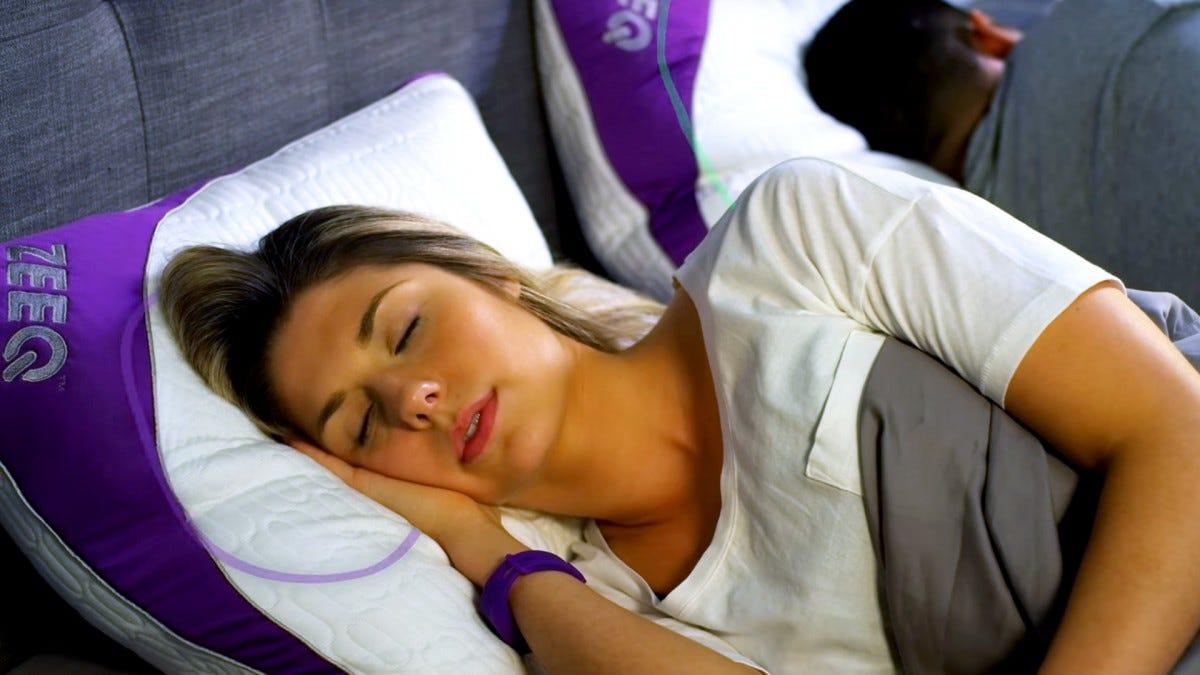 A woman sleeping on a Zeeq smart pillow