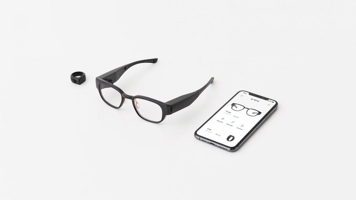 A pair of Focals smart glasses, a ring controller, and a phone displaying a smart glasses app.