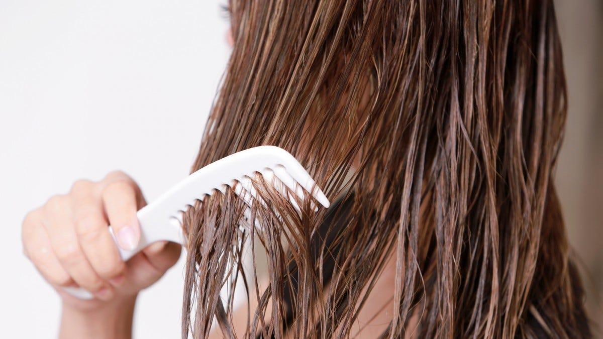 A woman hand running a comb through long, wet hair.