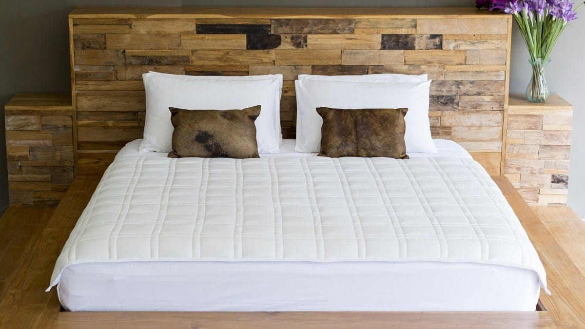 Weighted, white blanket on a wooden platform bed.