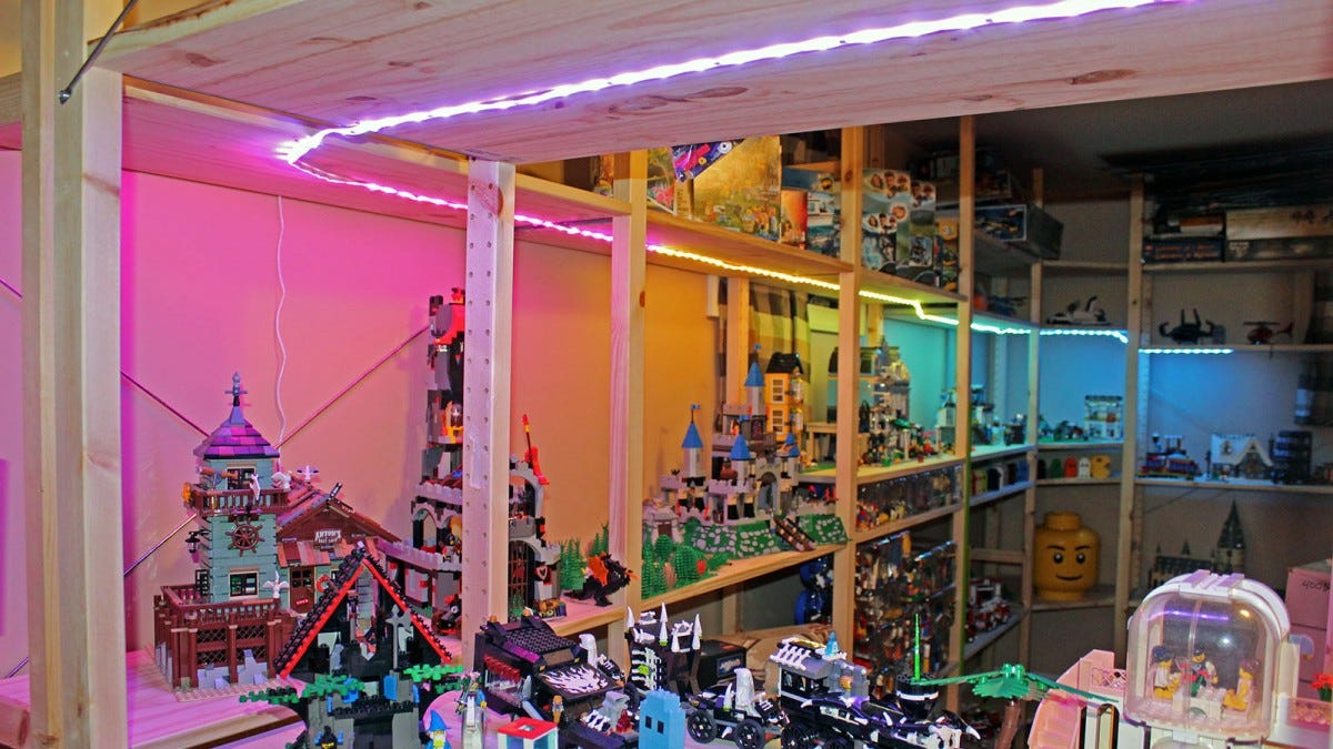 A shelf filled with Lego Bricks, and a single light strip with purple, yellow and blue colors.