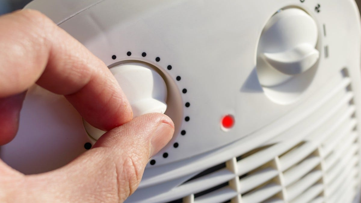 A man's hand turning a knob on a space heater.