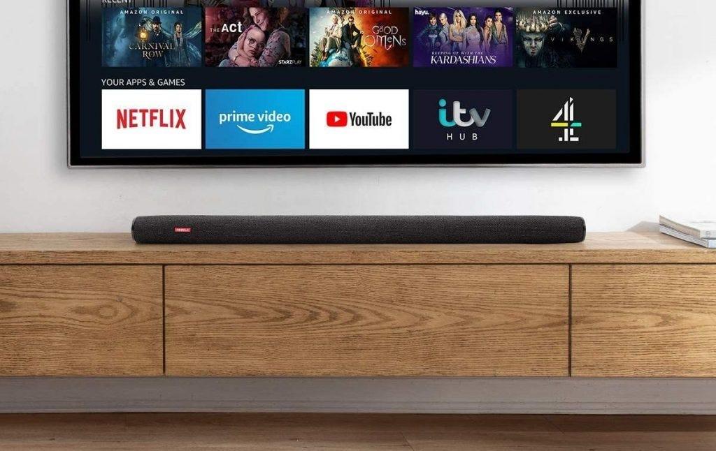 Soundbar ngồi trên một chiếc tủ bên dưới TV