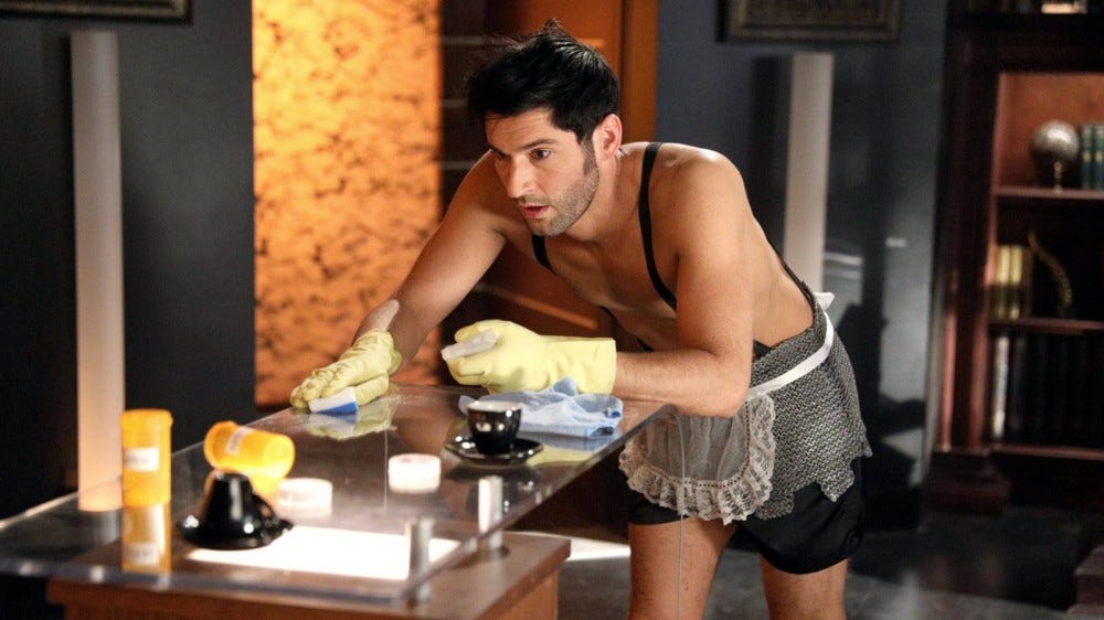 Lucifer in a french maid's outfit, cleaning a counter topped with drugs.