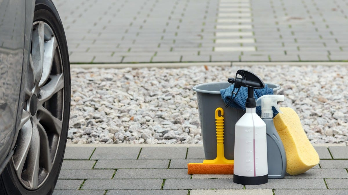 A bundle of cleaning supplies on the ground next to a car.