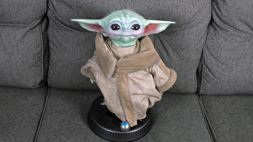 A Baby Yoda replica staring up into the camera.