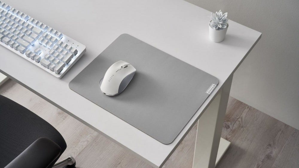 A Razer mouse, mousepad, and keyboard in soft white and silver colors.