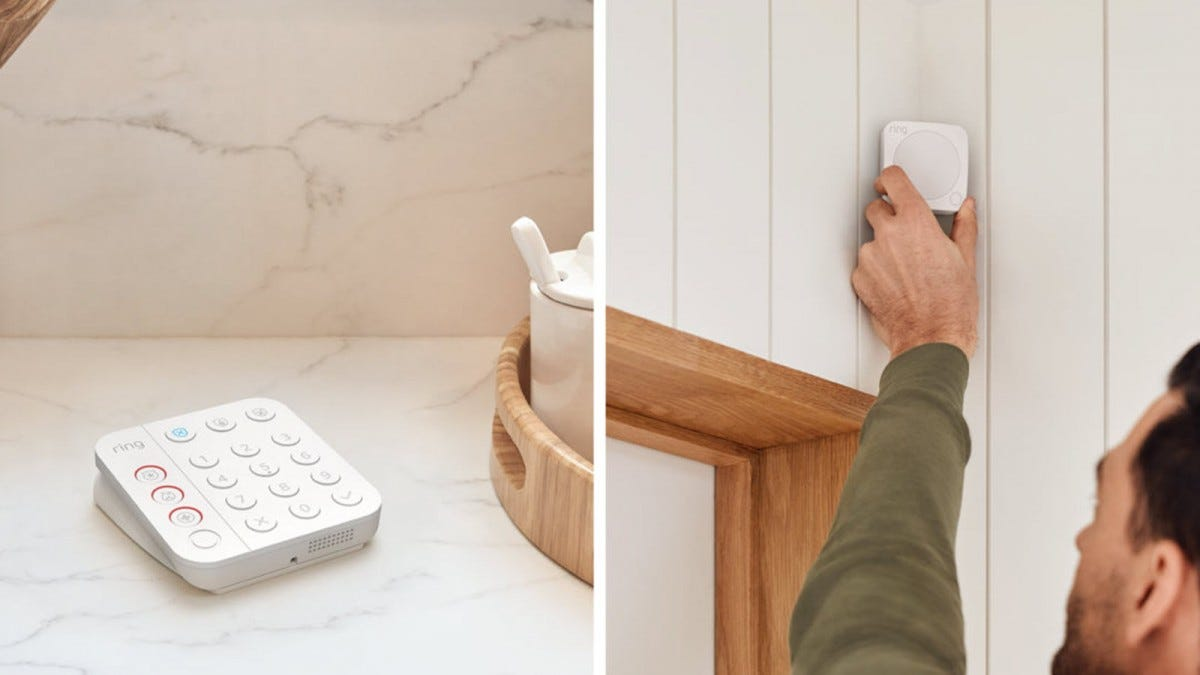 A Ring second generation keypad on a desk, while a man hangs a second generation motion detector.