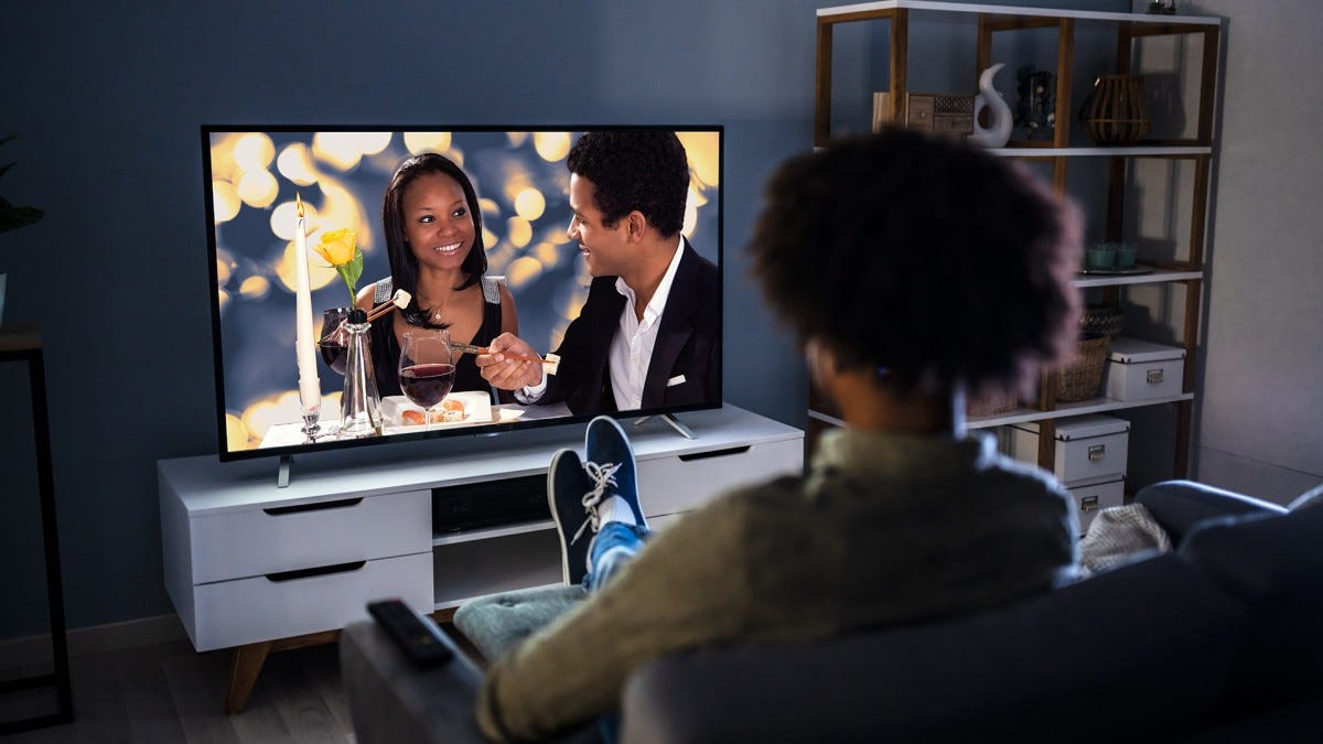 A young woman streams a soap opera on her 4k TV.