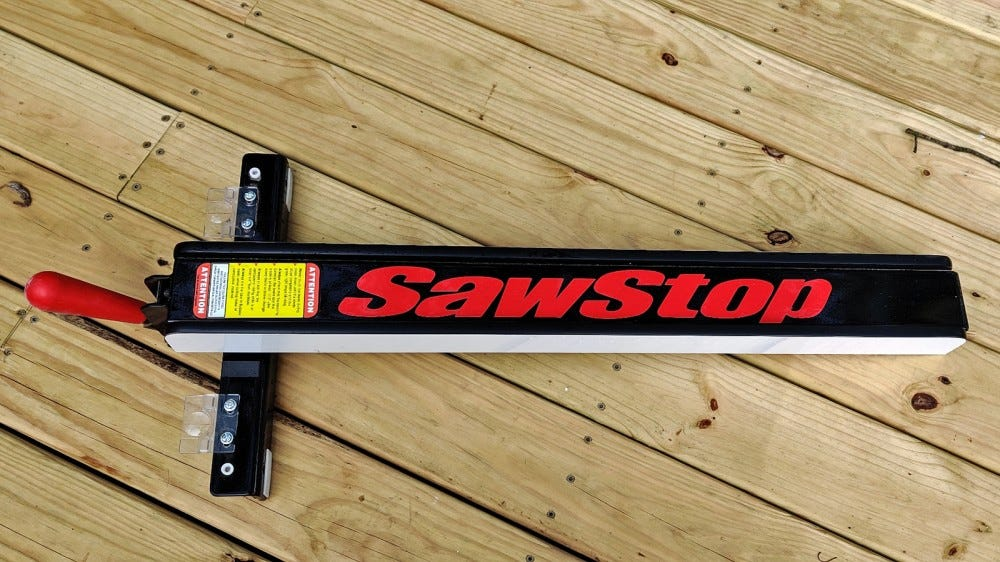 A closeup of a Sawstop T-Glide fence on a wood deck.