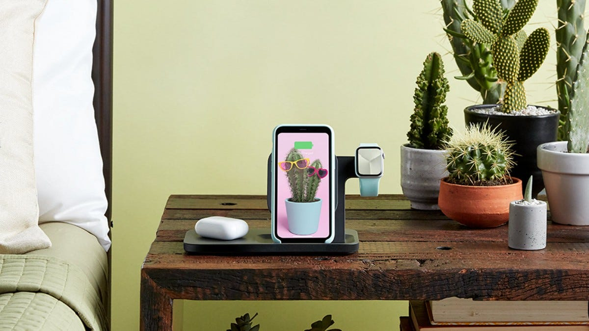 The Logitech 3-in-1 dock charging Airpods, an iPhone, and an Apple watch on a rustic nightstand.