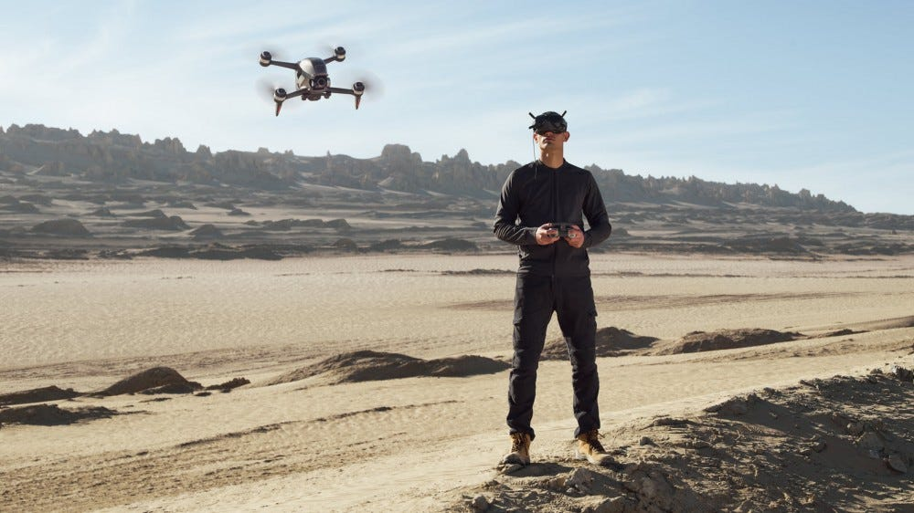 A man flies a drone while wearing safety goggles over his eyes.