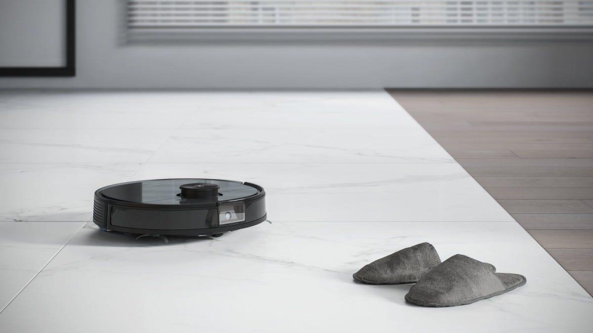 An Ecovacs robot vaccumm avoiding a pair of slippers.