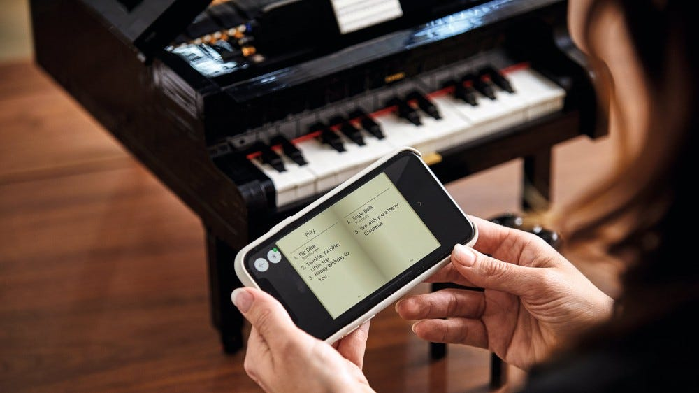 SOmeone holds a phone that shows songs over LEGO Grand Piano