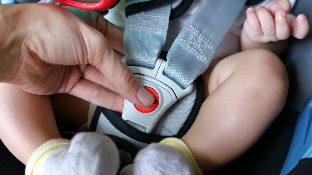 An infant being buckled into a car seat