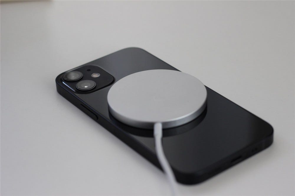 The black iPhone 12 Mini with the MagSafe wireless charger connected