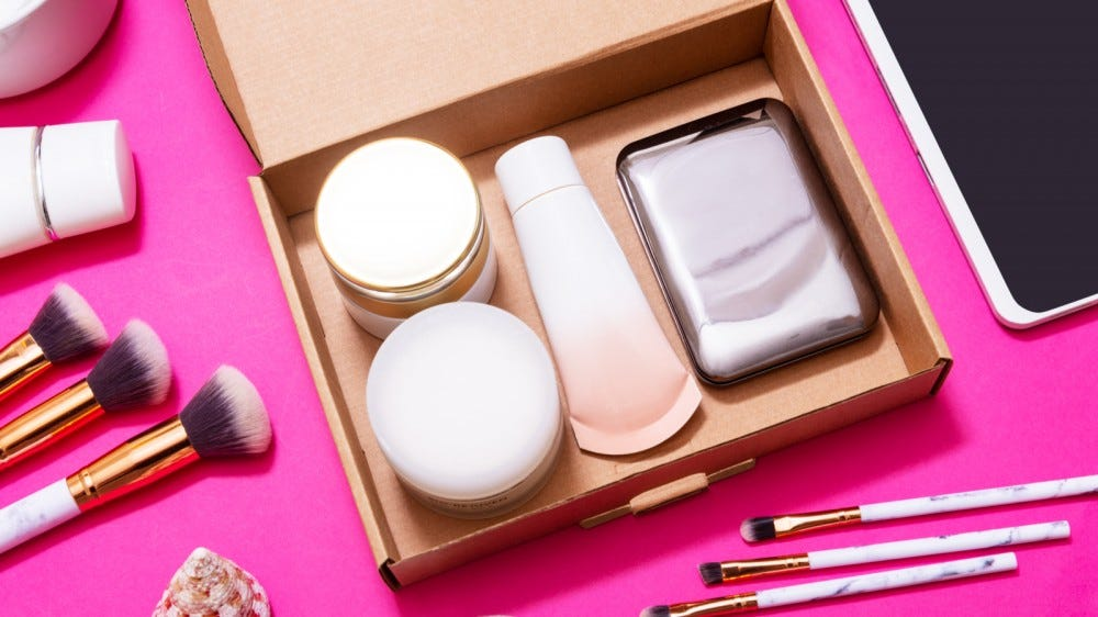 Digital tablet and makeup subscription boxes on pink table